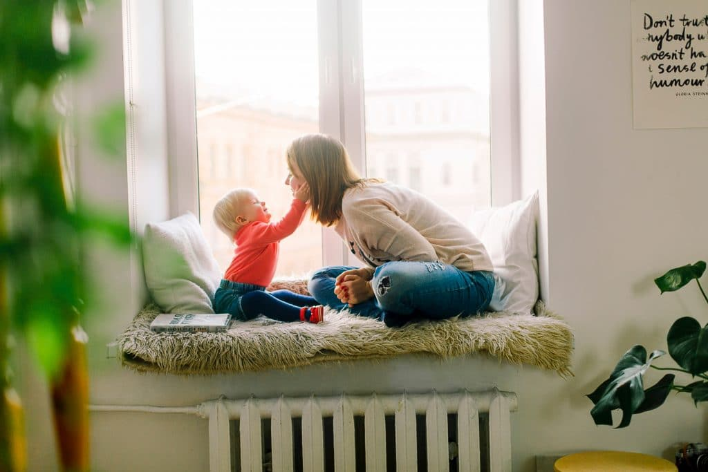 Young Child Touching Mothers Face In Window Seat